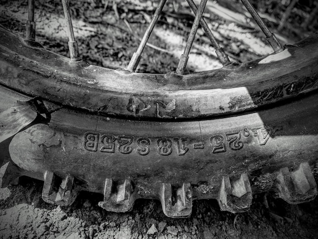 Closeup foto de escala de grises de un neumático de motocicleta en el suelo fangoso