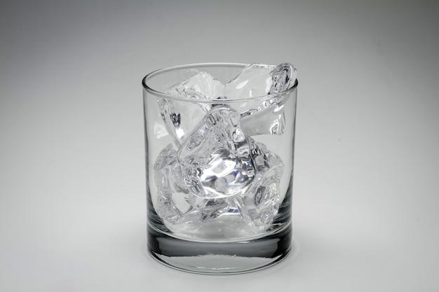 Closeup foto de escala de grises de un vaso lleno de cubitos de hielo aislado