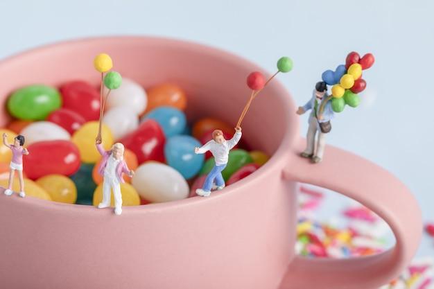 Closeup foto de figuras de personas con globos en una taza con caramelos de colores