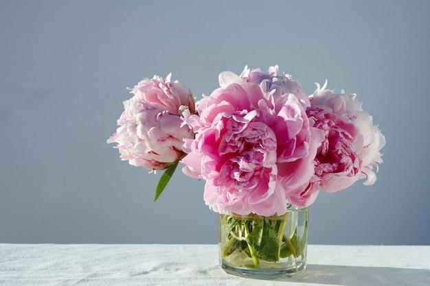 Closeup foto de hermosas peonías rosas en un frasco de vidrio corto en mesa gris