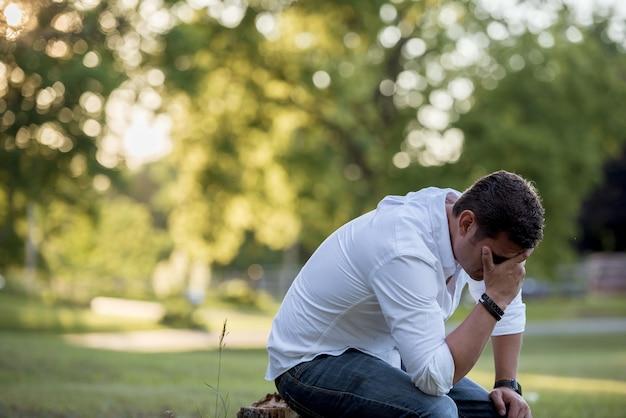 Closeup foto de un hombre en el suelo con la mano en la cara y un fondo borroso