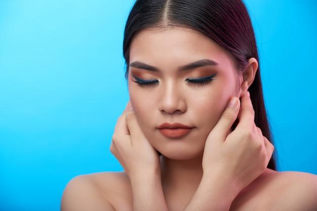Closeup foto de joven asiática con maquillaje posando con los ojos cerrados y las manos tocando las mejillas