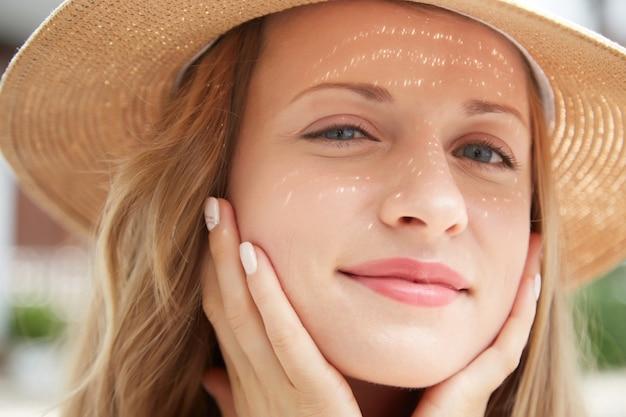 Closeup foto de joven caucásica en un sombrero de paja tocando suavemente su rostro