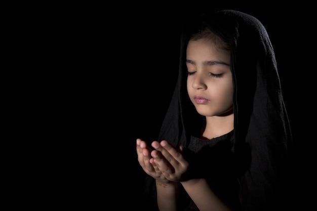 Closeup foto de una joven mujer rezando con los ojos cerrados en la pared negra