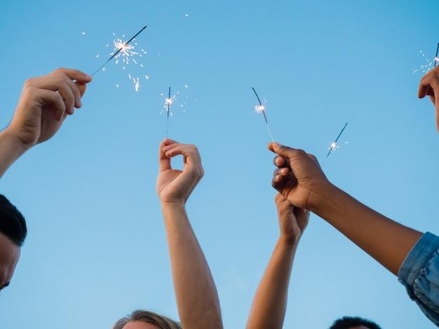 Closeup foto de jóvenes con luces de bengala en manos levantadas. grupo de amigos divirtiéndose en la fiesta al aire libre. concepto de celebración