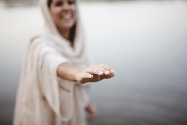 Closeup foto de una mujer que llevaba una túnica bíblica con la mano hacia la cámara