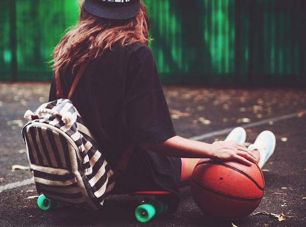 Closeup foto pelota de baloncesto con niña sentada en plástico naranja penny shortboard sobre asfalto