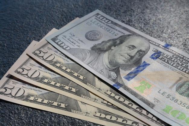 Closeup foto de tres billetes de cincuenta y cien dólares