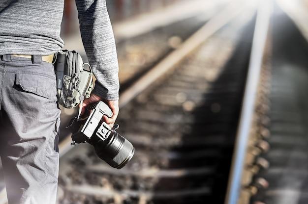 Closeup fotografía sosteniendo una cámara profesional con espacio de copia en la estación de tren.