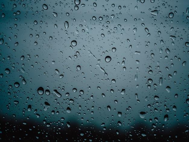 Closeup gotas de lluvia sobre el coche de cristal en la temporada de lluvias.
