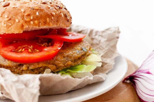 Closeup hamburguesa de quinua vegetariana con tomate, cebolla y pan de hamburguesa.
