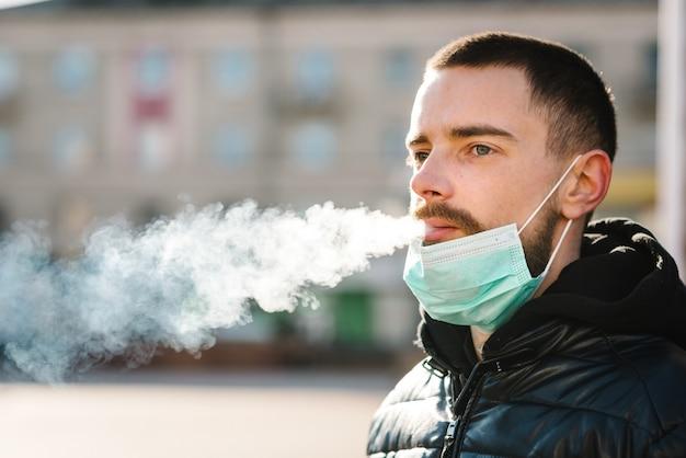 Closeup hombre con máscara durante la pandemia de covid-19 fumando un cigarrillo en la calle.