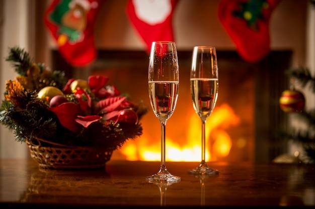 Closeup imagen de champán gaseoso en dos copas en la mesa de navidad frente a la chimenea
