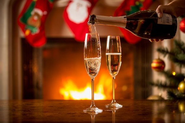 Closeup imagen de dos vasos llenos de champán en la mesa de navidad frente a la chimenea