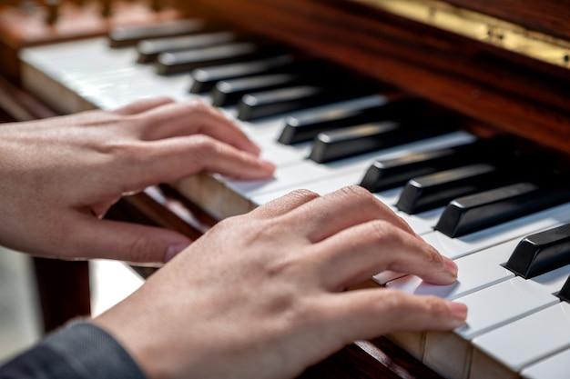 Closeup imagen de manos tocando un piano de cola de madera vintage