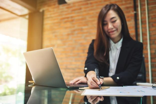 Closeup imagen de mujer de negocios escribiendo en el papeleo mientras trabajaba en la computadora portátil en la oficina