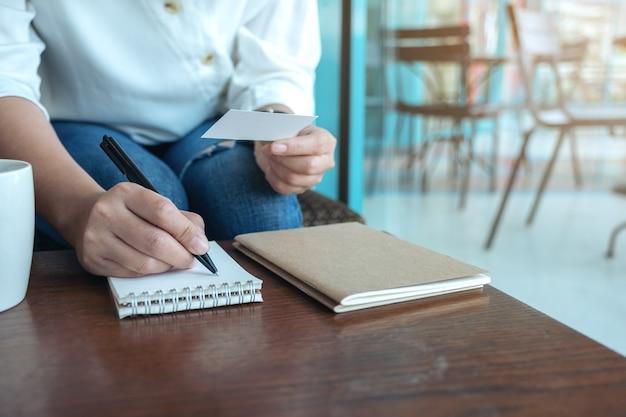 Closeup imagen de una mujer sosteniendo una tarjeta de presentación vacía en blanco mientras escribe en un cuaderno