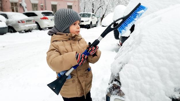 Closeup imagen de niño con abrigo beige limpiar el coche después de la tormenta de nieve con un cepillo