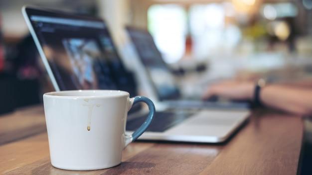 Closeup imagen de personas trabajando y escribiendo en el teclado del ordenador portátil con una taza de café sobre la mesa en la oficina