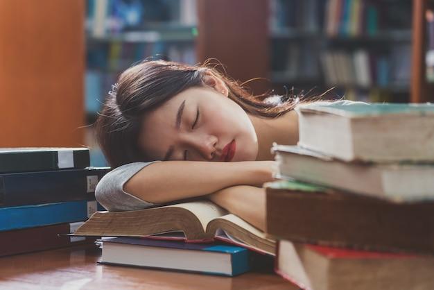 Closeup joven estudiante asiática en traje casual leyendo y durmiendo en la mesa de madera con varios libros en la biblioteca de la universidad