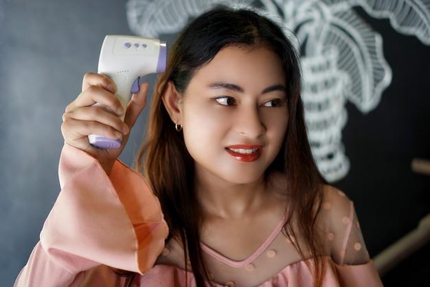 Closeup joven mujer asiática adulta mantenga equipo termómetro infrarrojo midiendo la temperatura corporal en la cabeza