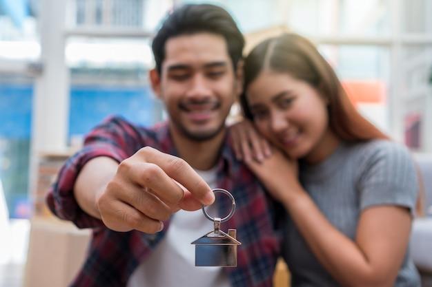 Closeup joven pareja asiática sosteniendo el llavero de la casa en el amor y la sensación alegre