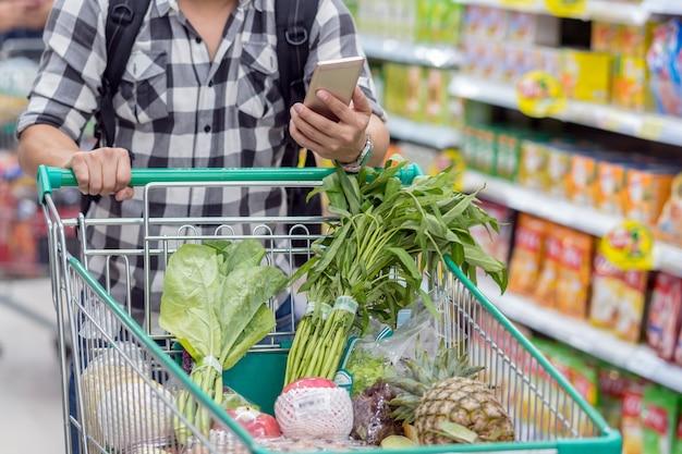 Closeup jóvenes asiáticos usando el teléfono móvil inteligente para comprobar el producto
