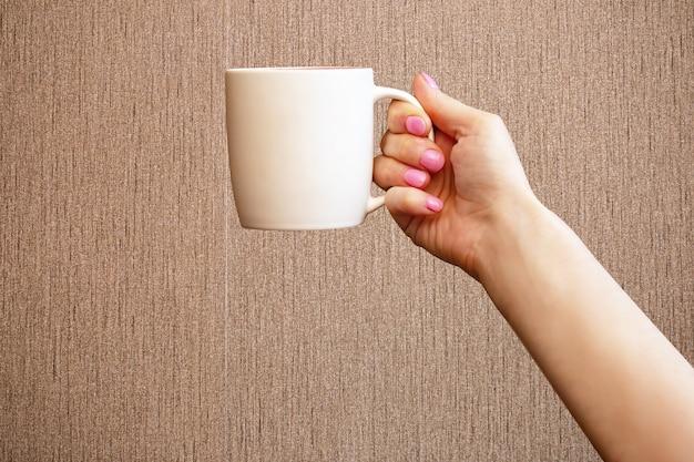 Closeup mano femenina caucásica sosteniendo una taza blanca de té o café por la mañana sobre fondo marrón con
