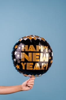 Closeup mano femenina sosteniendo negro feliz año nuevo globo aislado sobre azul