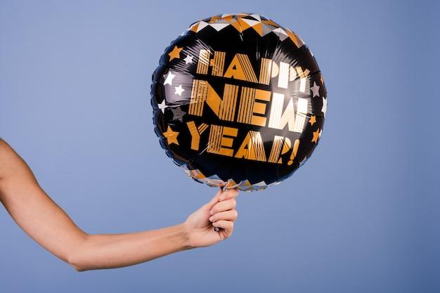 Closeup mano femenina sosteniendo negro feliz año nuevo globo