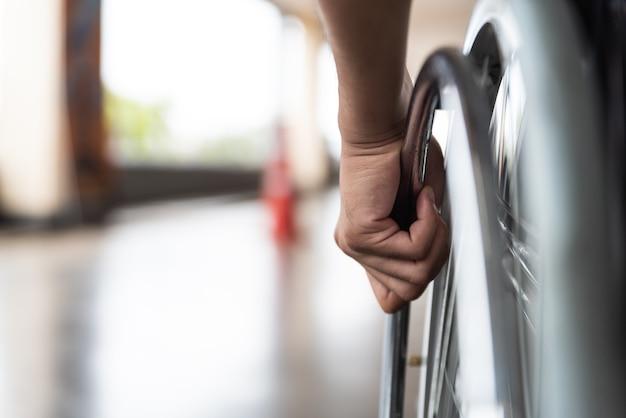 Closeup mano de hombre con discapacidad en la rueda de la silla de ruedas.
