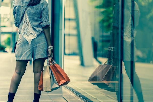 Closeup mano sosteniendo las bolsas de compras al lado de los vasos de tienda tienda