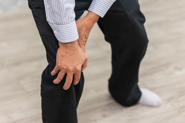 Closeup mano sosteniendo dolor de rodilla anciano.