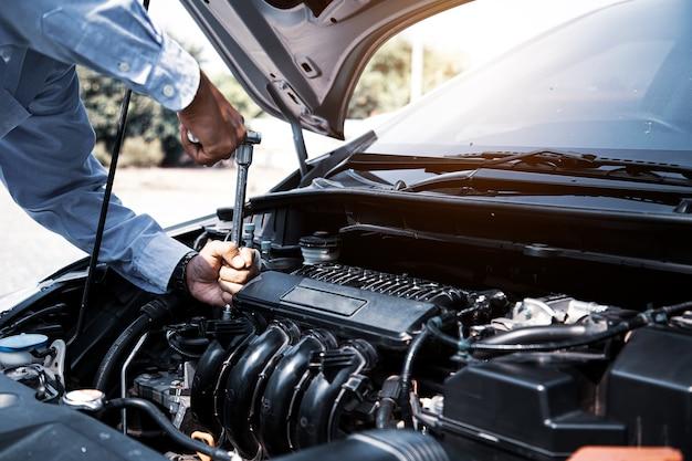 Closeup manos de mecánico de automóviles están utilizando la llave para reparar el motor de un automóvil en el garaje de automóviles