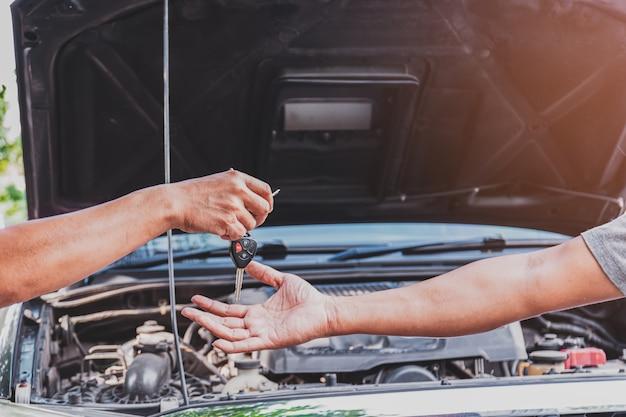 Closeup a manos del mecánico está devolviendo las llaves a los clientes que han reparado el automóvil en el garaje después de realizar las reparaciones, el transporte y los conceptos de la industria de seguros.