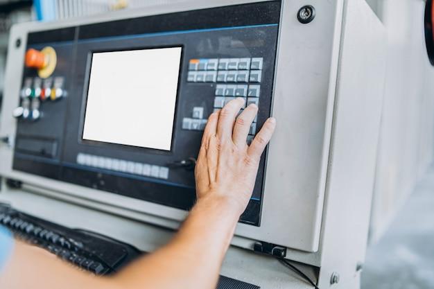 Closeup manos de trabajador cerca de la computadora en la fábrica de fabricación.