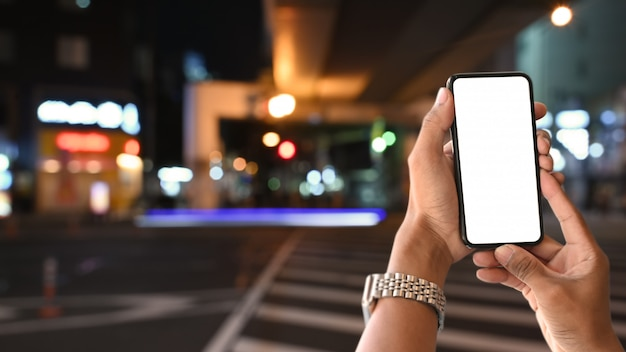 Closeup maqueta smartphone en mano del hombre en el paisaje de la ciudad en japón.