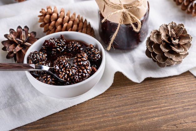 Closeup mermelada de conos de pino joven en un tazón blanco con conos y tarro en una toalla de cocina blanca sobre la mesa de madera
