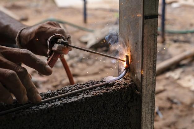 Closeup metal de soldadura manual en sitio de construcción