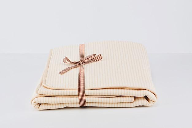 Closeup montón envuelto plegado manta de algodón beige natural en blanco