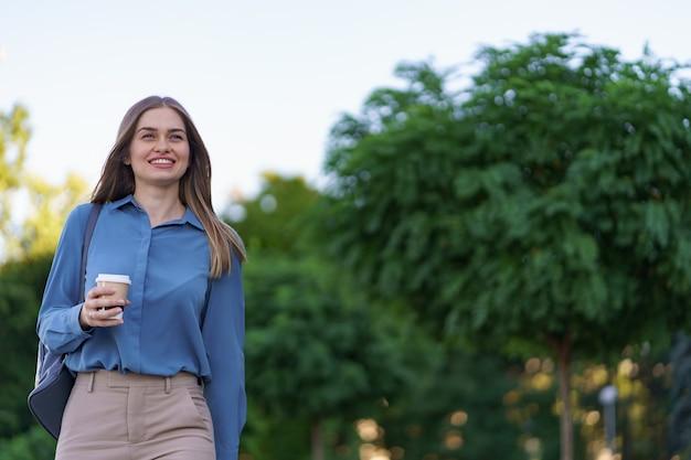 Closeup mujer atractiva en movimiento con café para llevar en las calles de la ciudad. retrato chica rubia sosteniendo un vaso de papel con bebida caliente al aire libre.
