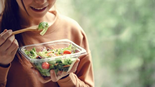 Closeup mujer comiendo ensalada de comida saludable, foco en ensalada y tenedor.