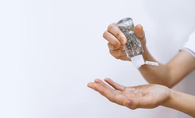Closeup mujer lavarse las manos con gel de alcohol 75% para prevenir la infección por virus y peste con enfoque suave y luz excesiva en el