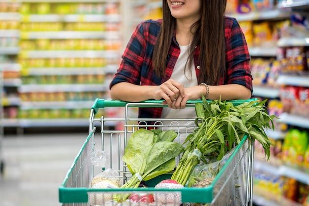 Closeup mujeres asiáticas jóvenes mano sosteniendo la carretilla para ir de compras en la tienda borrosa en el departamento