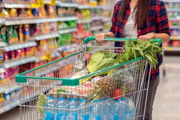 Closeup mujeres asiáticas jóvenes mano sosteniendo la carretilla para ir de compras