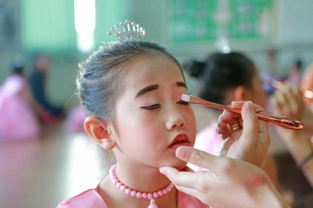 Closeup niña asiática con maquillaje de su madre.