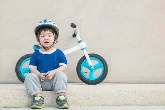 Closeup niño feliz con cara de sonrisa sentarse en el piso de piedra de mármol con bicicleta en la pared de piedra con textura de fondo con espacio de copia