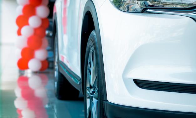 Closeup parrilla y rueda del nuevo suv de lujo blanco estacionado en sala de exposición moderna. concesionario de automóviles sala de exposición.