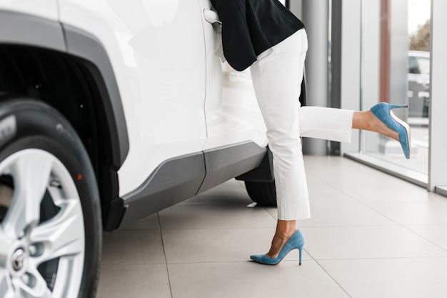 Closeup piernas femeninas - mujer se apoyó en el coche blanco.