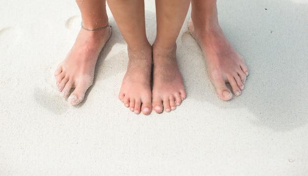 Closeup pies de una madre y un niño en la playa de arena blanca